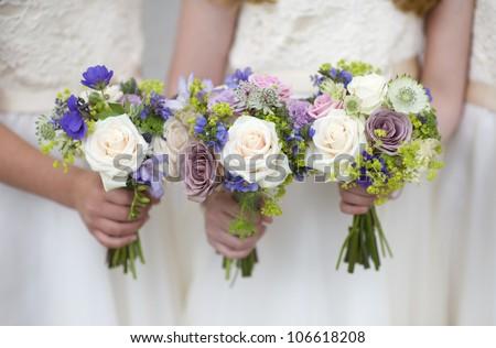three wedding bouquets held by bridesmaids or flowergirls