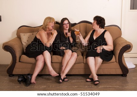 Three well dressed and diverse woman socializing with wine.