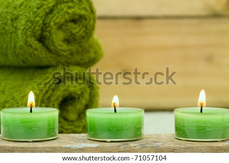 Three wellness candles and green towels - stock photo