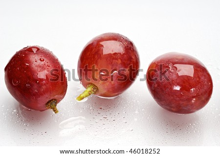 three wet red grapes isolated on white background