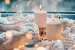 three white burning candles against the window with a white woolen scarf and blue wooden background