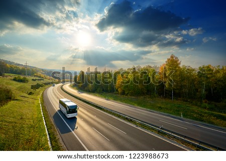 Three white buses traveling on the asphalt highway between deciduous forest in autumn colors under the radiant sun and dramatic clouds. View from above.