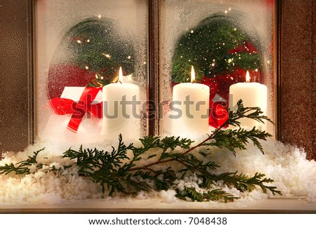 Three white candles in a frosted window
