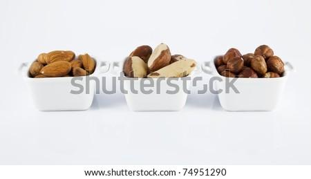 Three white ceramic bowls, with almond, Brazil nut and hazelnut.