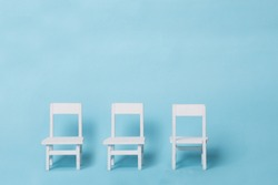 Three white chairs on a plain soft blue background. Two facing in front, one facing the opposite. Conceptual. Symbol of unique.