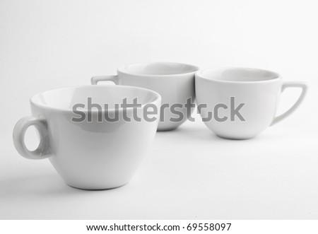 Three white cups on gray background - stock photo