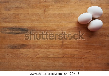Three white eggs sit on a butcher block counter with area suitable for text
