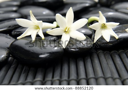 three white flower with spa stones  on bamboo stick straw mat