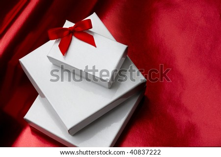 Three white gift boxes stacked on each other with red ribbon shot on red foil wrapping paper with space for copy