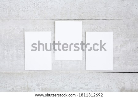 Three white greeting cards mockup on a white wooden desk. Blank, closed card template. Flat lay. ストックフォト ©