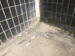 Three white plastic syringes with open needles lie on the gray textured asphalt in the corner near the house. The walls of the house are lined with black rectangular tiles. Drugs. Danger. Addiction.