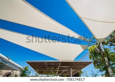 Three white sun shades in a spanish beach club. Urban scene in a Mediterranean tourism spot under blue sky on a sunny day #708174817