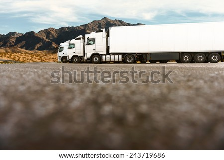 Three white trucks on a parking lot of a transportation company waiting for the next order. Low angle shot, copy space on the bottom of the image