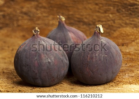 Three whole figs on old tree bark as background