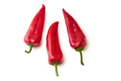 Three whole red bell peppers isolated on white background