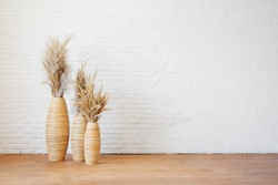Three wicker vases with dry pampas grass against a white textured brick wall. Blank for interior design in boho or scandinavian style.