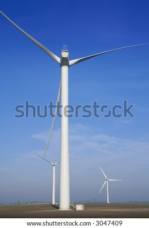 Three wind power generators in flat farmland with blue sky - stock photo