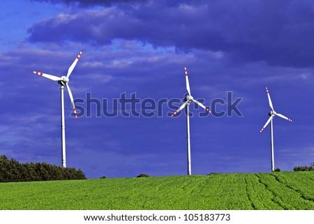 Three wind turbines before storm