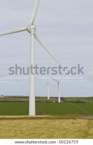 Three wind turbines in the Welsh countryside