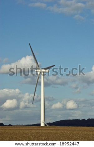 Three windmills under a blue sky in the English countryside