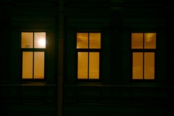 Three windows of an apartment building lit in the dark of night