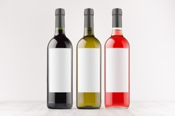 Three wine bottles - red, green, black - with blank white labels on white wooden board, mock up. Template for advertising, design, branding identity.