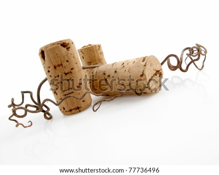 Three wine corks with grapevine tendrils on white
