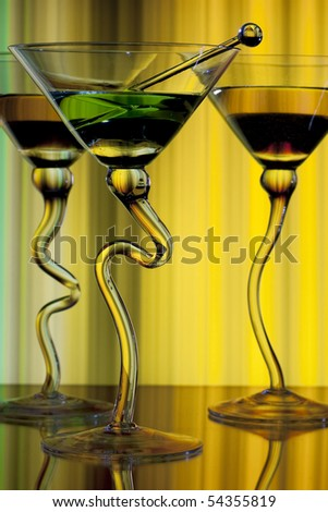 Three wine glasses with curved stems full of liqueur on yellow background