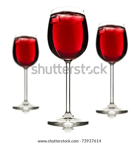 Three wine glasses with red fruit juice and ice on a white background