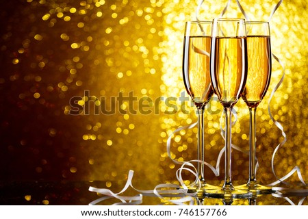 Three wine glasses with sparkling champagne with white ribbons on yellow background #746157766