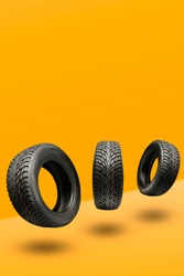 three winter tires friction on a bright orange background. seasonal change of wheels for winter. vertical photo copyspace