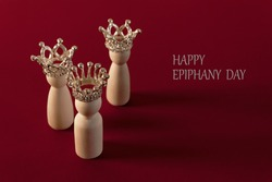 Three wise men figures with crowns on red background and the text Happy Epiphany day. Copy space.