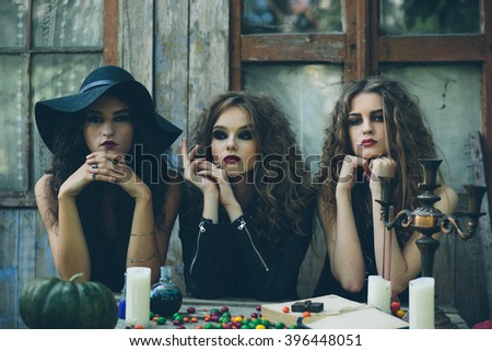 three witches are sitting at a table on the eve of Halloween #396448051