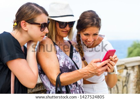 Three woman looking to the smart-phone mobile phone searching for the tourist information photos in the Corfu town