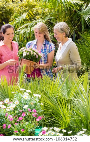 Three woman shopping potted flowers at garden centre green house