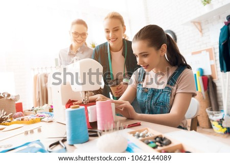 Three women at garment factory. One of them is sewing new dress. They are happy and fashionable. - Shutterstock ID 1062144089