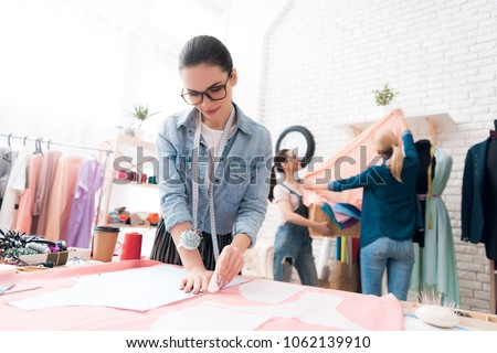 Three women at garment factory. They are taking measurements and making cut-out. They are happy and fashionable. #1062139910