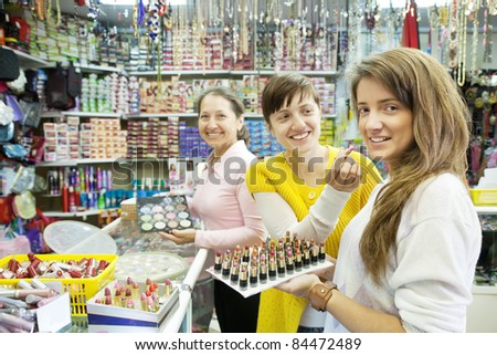Three women chooses   lipstick at cosmetics  shop - stock photo