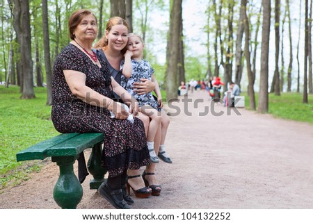 Three women different ages are sitting on bench in park. Grandmother, mother and small daughter