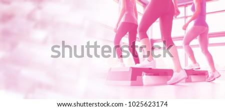 Three women doing aerobics against glowing background
