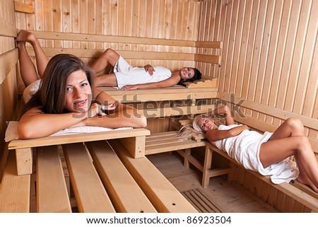 Three women enjoying a hot sauna, having a casual chat