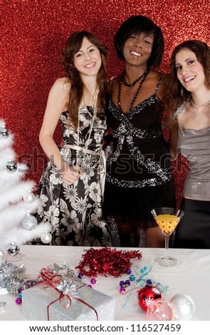 Three women friends smiling at a christmas party, having fun with a white decorated tree in a red glitter background.