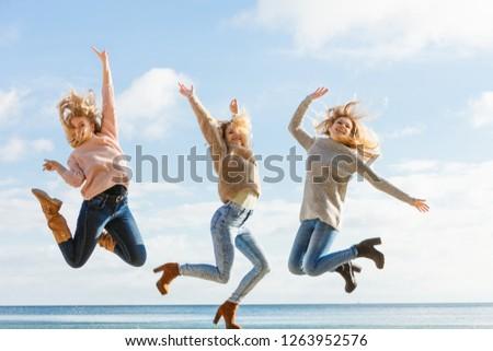44cea8eab0c7b Three women full of joy jumping around with sky in background. Female  friends having fun