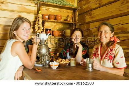 three women having tea in russian traditional interior