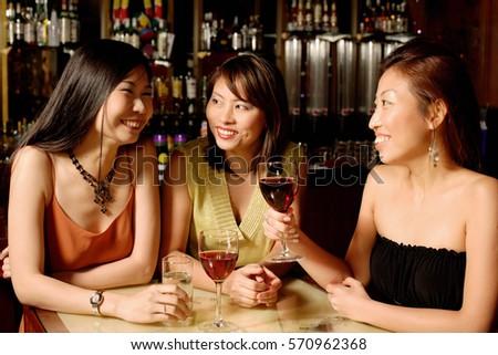 Three women holding wine glasses #570962368
