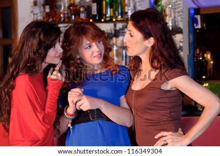 Three women in a bar sharing stories, bottles of liquor seen in the background.