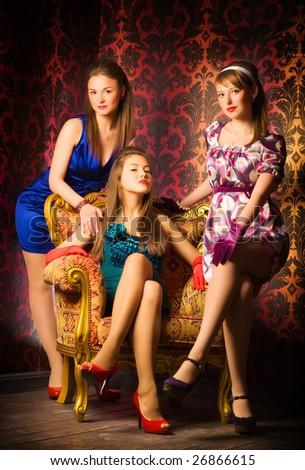 Three women in a luxury interior. Retro style.