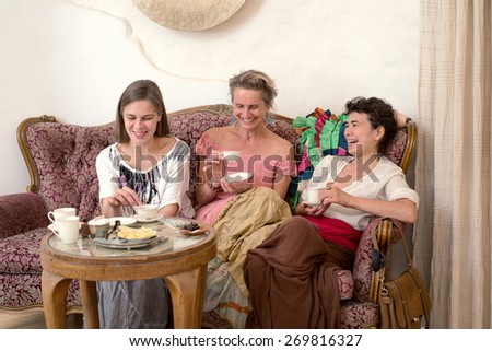 Three women in ethnic dresses sitting on an old couch and drinking tea