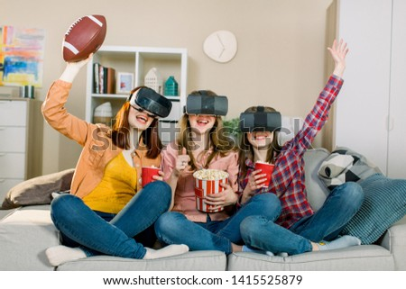 Three women in modern virtual reality headsets having expirience in watching football match at home. Girls in vr glasses sitting on the sofa and eating popcorn