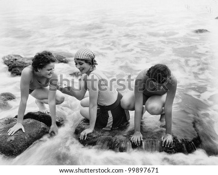 Three women playing in water on the beach